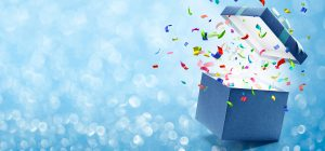 confetti of multiple colors popping out of a blue box with a blue background with sparkles
